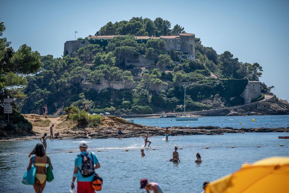 Frankreich, Bormes-Les-Mimosas: Badegäste schwimmen unterhalb der Sommerresidenz des Staatschefs von Frankreich, Macron, dem Fort de Bregancon am Mittelmeer.