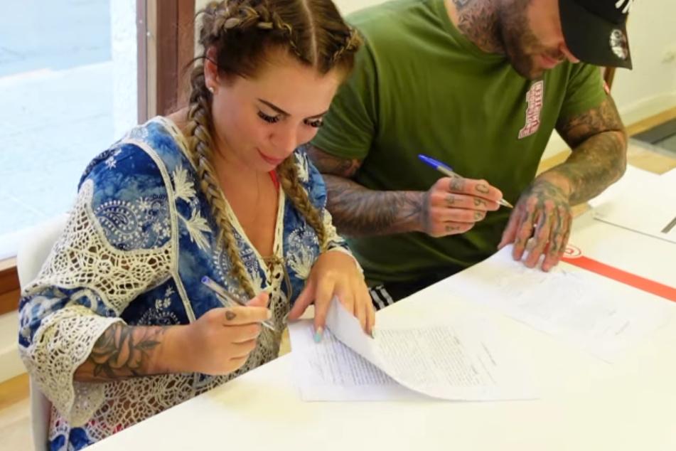 Jenny und Steffen unterzeichnen offenbar Vertragsunterlagen im Makler-Büro.