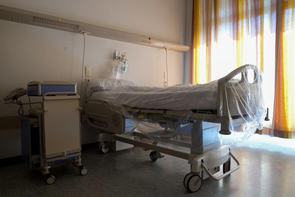 Ein mit Folie überzogenes Bett steht in einem Krankenhauszimmer.