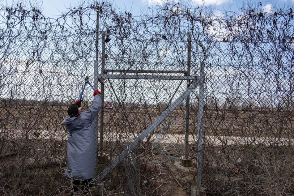 Ein Migrant steht am Grenzzaun an der türkisch-griechischen Grenze in Pazarkule und versucht, ihn mit einer Drahtschere zu durchschneiden.
