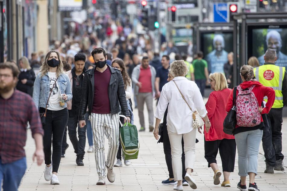 Fußgänger tragen beim Einkaufen auf der Princes Street in Edinburgh Schutzmasken.