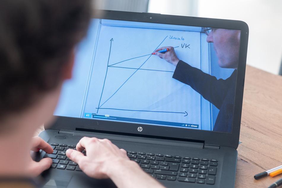 Constantin Pittruff, Student, sitzt zu Hause vor einem Laptop, auf dem ein Erklärvideo seiner Universität läuft.