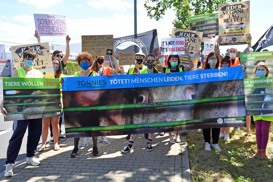 """2. Juli, Weißenfels: Aktivistinnen und Aktivisten des Deutschen Tierschutzbüros demonstrieren vor dem Tönnies-Schlachthof. Die Teilnehmer haben sich unter dem Motto """"Tönnies tötet - Menschen leiden, Tiere sterben"""" versammelt."""