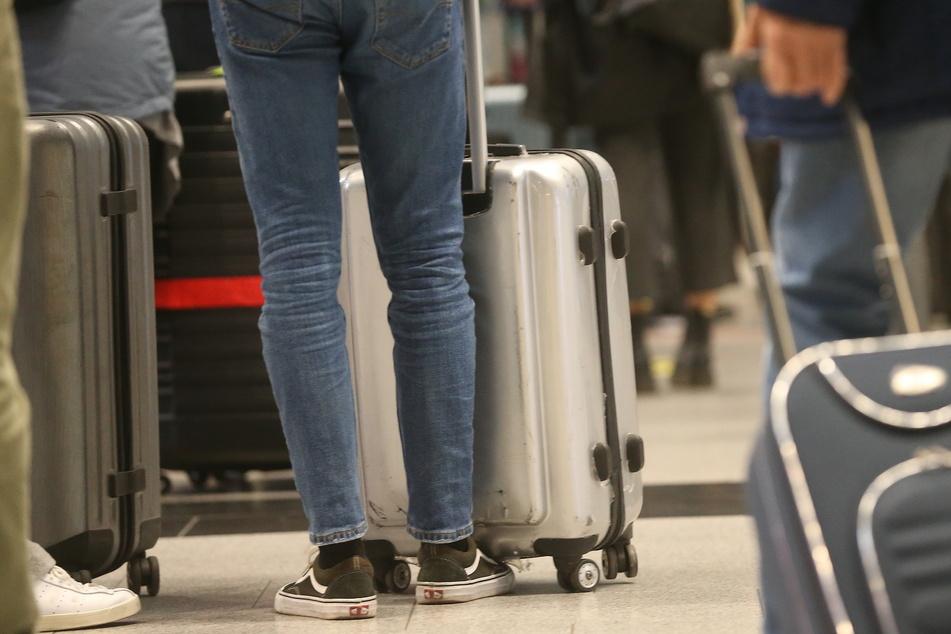 Nordrhein-Westfalen, Düsseldorf: Passagiere stehen mit ihrem Gepäck am Flughafen Düsseldorf in einer Schlange, um für einen Eurowings-Flug nach Palma de Mallorca einzuchecken.