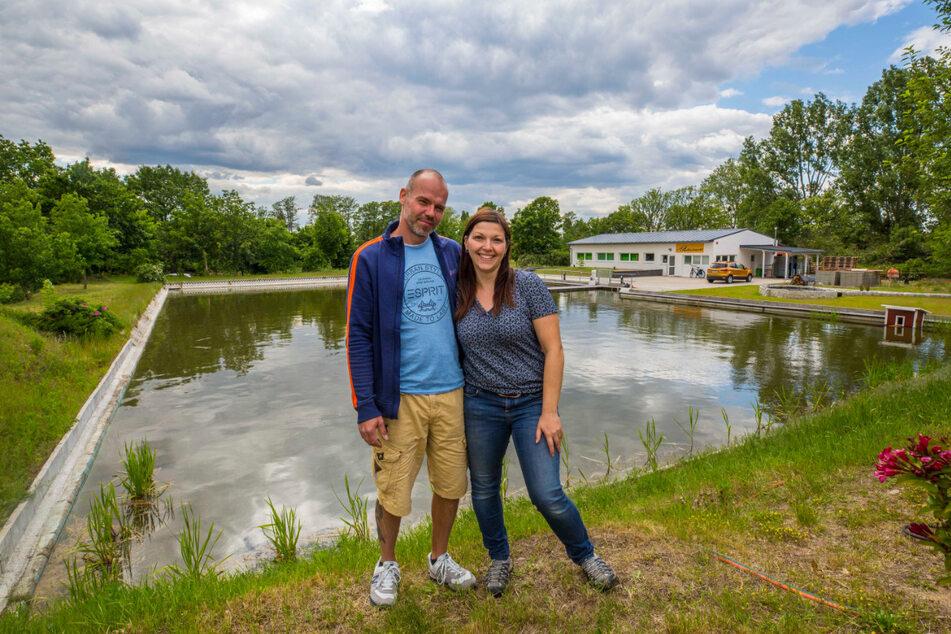 Ronald Reinert (42) und Sylvia Grimm (38) vor ihrem Angelteich (früher das Schwimmbecken) im ehemaligen Waldbad in Zeißig. Im Hintergrund: der neu eröffnete Angelfachmarkt.