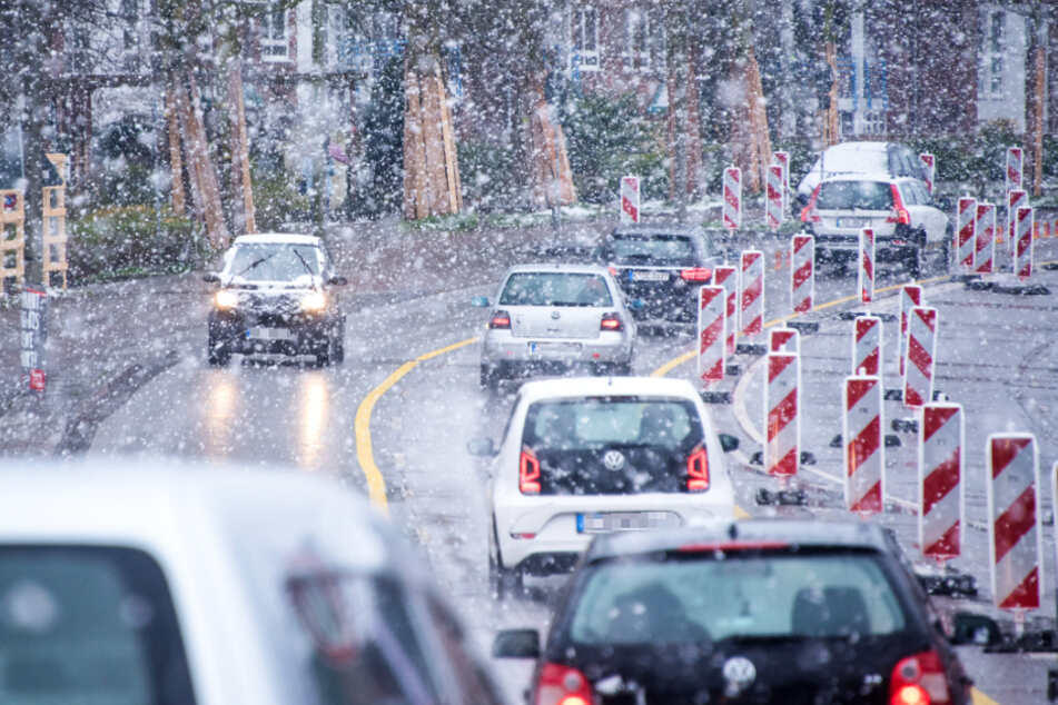 Es schneit auf einer viel befahrenen Straße in Hamburg. (Symbolfoto)