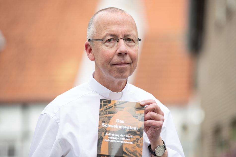 """Der Autor und Pfarrer Peter Kossen aus Lengerich hält bei der Vorstellung das Buch """"Das Schweinesystem""""."""