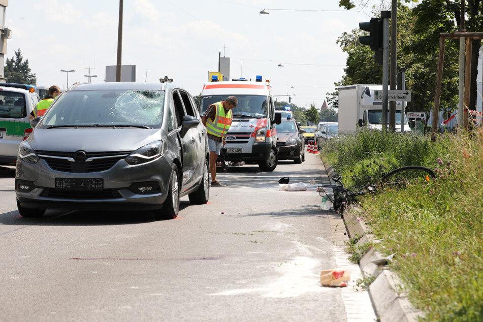 Das Fahrrad liegt rechts im Grünstreifen. Der beschädigte Opel steht an der Unfallstelle.
