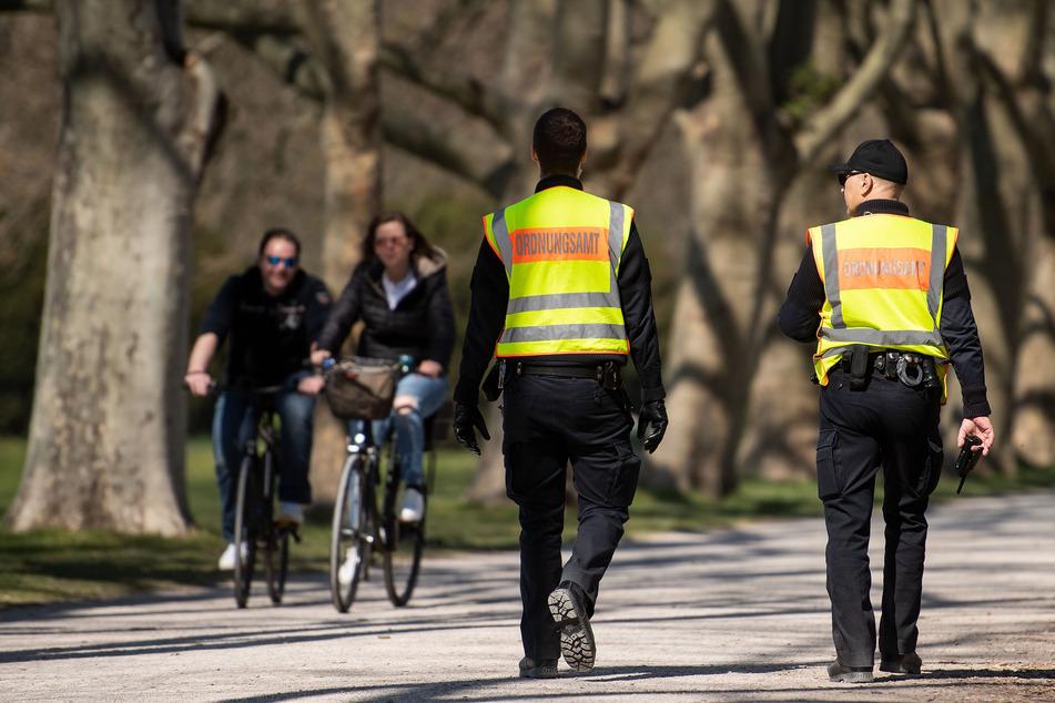 Mitarbeiter des Ordnungsamts kontrollieren in einem Park die Einhaltung der Schutzmaßnahmen gegen die Verbreitung des Coronavirus.