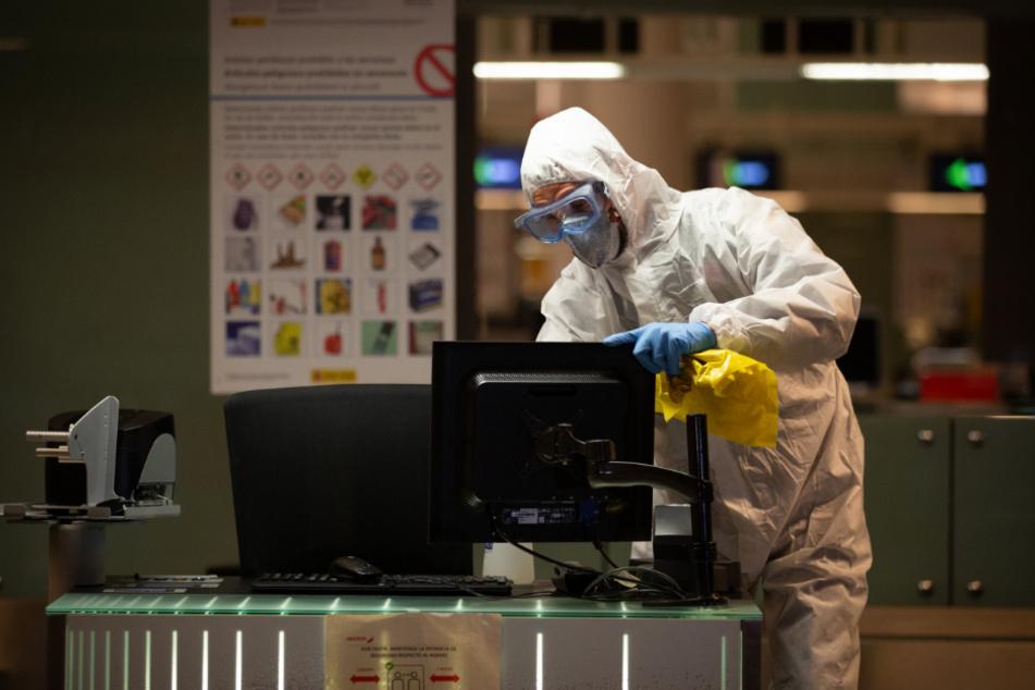 Ein spanischer Agent der militärischen Notstandseinheit reinigt einen Computer während den Desinfektionsaufgaben am Flughafen in Barcelona.