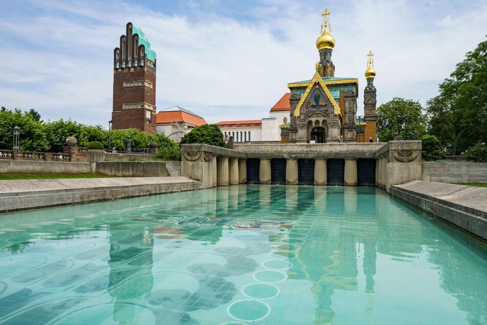 Der Hochzeitsturm (l.), das Ausstellungsgebäude (M.) und die russische Kapelle (r.) spiegeln sich auf der Mathildenhöhe im Lilienbecken.