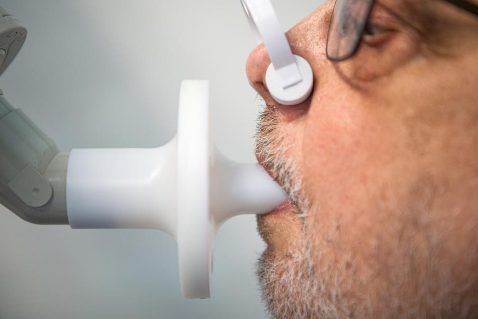 Ein Mann sitzt zur Überprüfung seiner Lungenfunktion in einem Bodyplethysmographen. In einer Klinik am Teutoburger Wald werden Long-Covid-Patienten behandelt. Eine entsprechende Therapie soll langfristig aus Baden-Württemberg kommen. (Symbolbild)