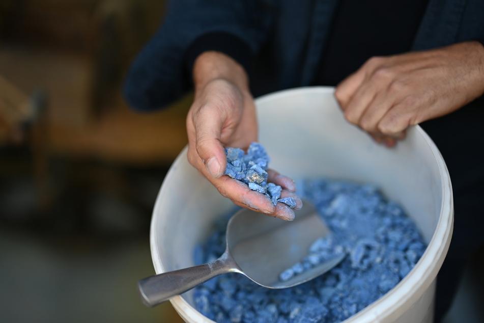 Kremer zeigt blaue Azurit-Steine, die fein gemahlen werden. Der Familienbetrieb im Allgäu stellt als einer der letzten weltweit historische Pigmente her.