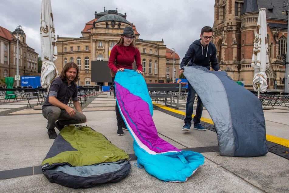 Filmnächte-Veranstalter Michael Claus (42), Janice Schmelzer (16) und ihr Freund Yannik Hinze (17) rollen die Schlafsäcke auf dem Theaterplatz aus.