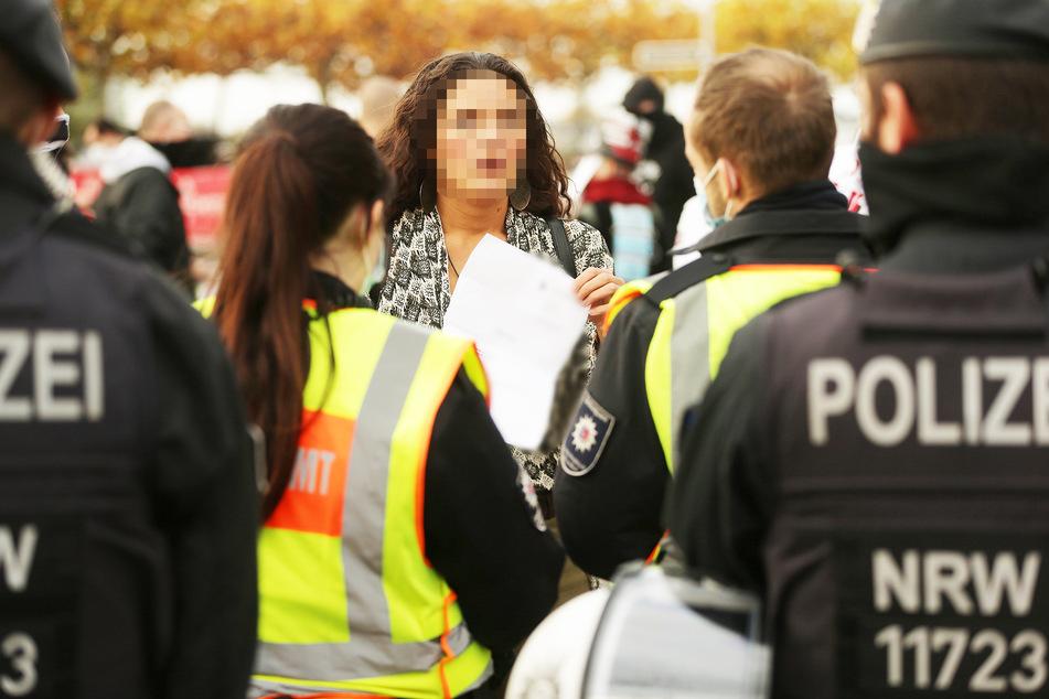 Eine junge Frau mit einem ärztlichen Attest, das sie vom Tragen eines Mund-Nasen-Schutzes freistellt, wird von der Polizei kontrolliert.