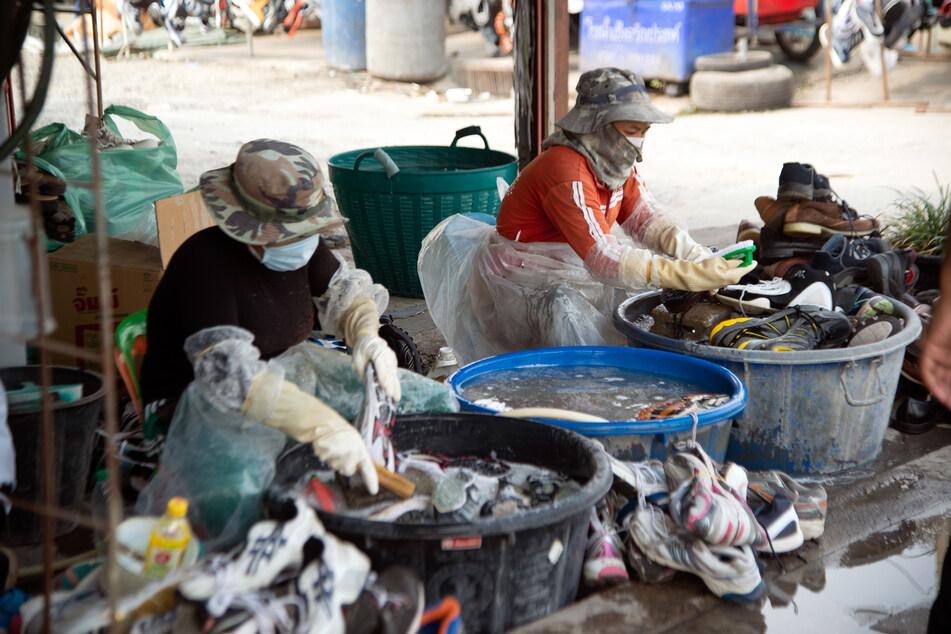 Angst vor COVID-19: In Thailand schützen sich die Menschen beim Waschen ihrer Schuhe mit Masken und Handschuhen.