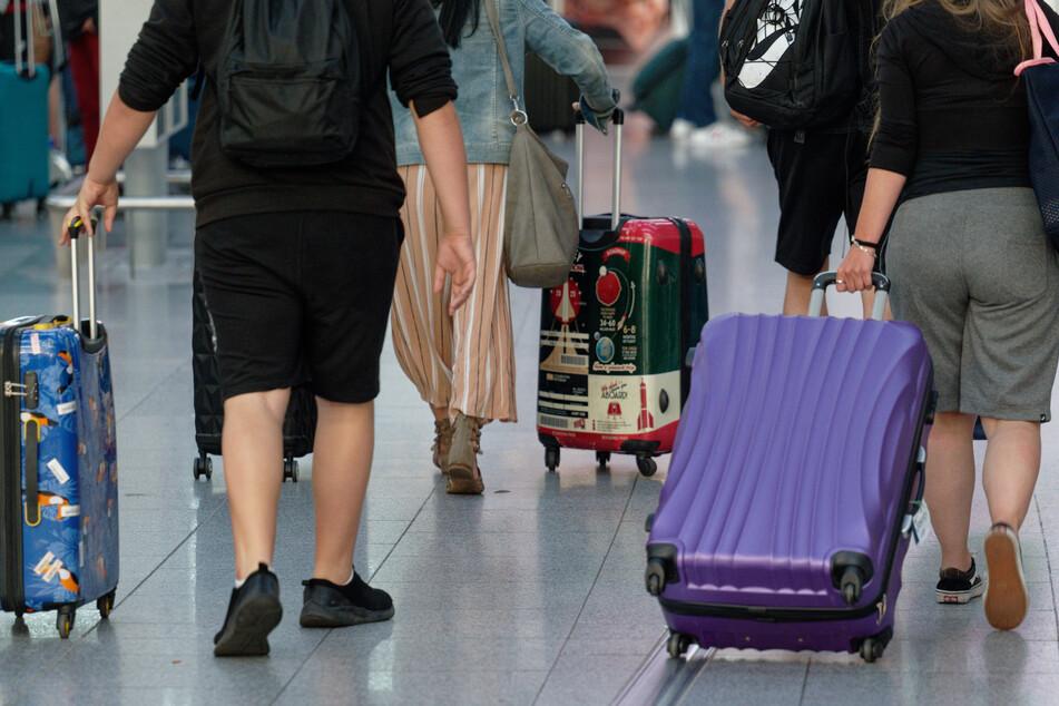 Reisende gehen in einem Flughafen mit Koffern durch die Abflughalle.