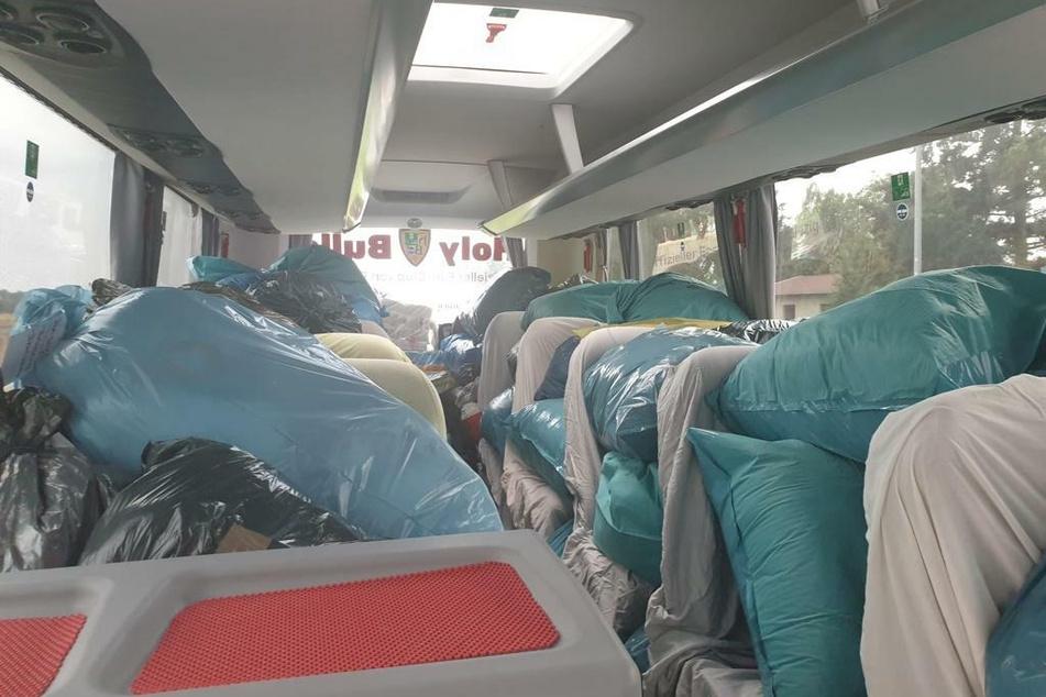 An Bord des Busses häufen sich Dinge des täglichen Bedarfs, Gummistiefel, Nahrung. Alles, was die Menschen vor Ort dringend brauchen.