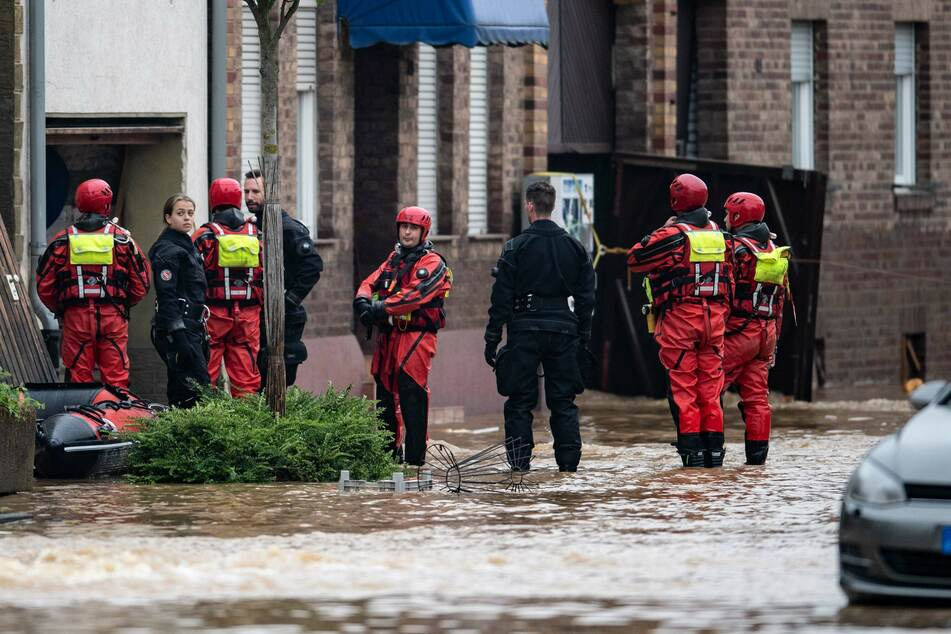 Rettungsschwimmer und Polizeitaucher sind mit Schlauchbooten im Einsatz, um Menschen auf ihren überfluteten Häusern zu retten.