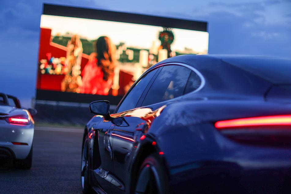 Besucher stehen mit ihren Autos in einem Autokino auf der Rundstrecke des Leipziger Porsche Werks.