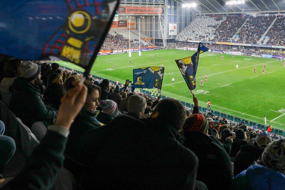 Zuschauer sitzen während eines Rugby-Spiels zwischen den Otago Highlanders und den Waikato Chiefs im Stadion.