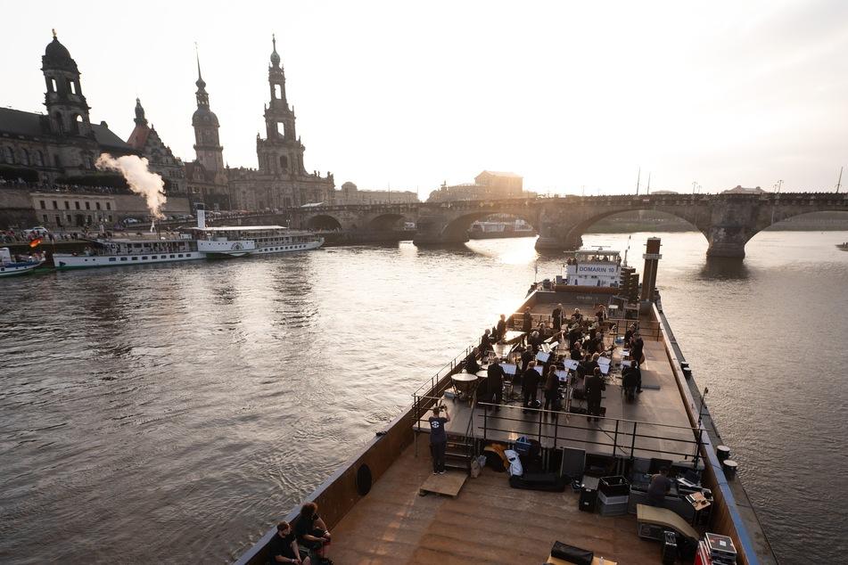 """Musiker der Dresdner Sinfoniker stehen während des Konzerts """"Elbkarawane"""" auf einem Schubverband vor der Kulisse der Dresdner Altstadt."""