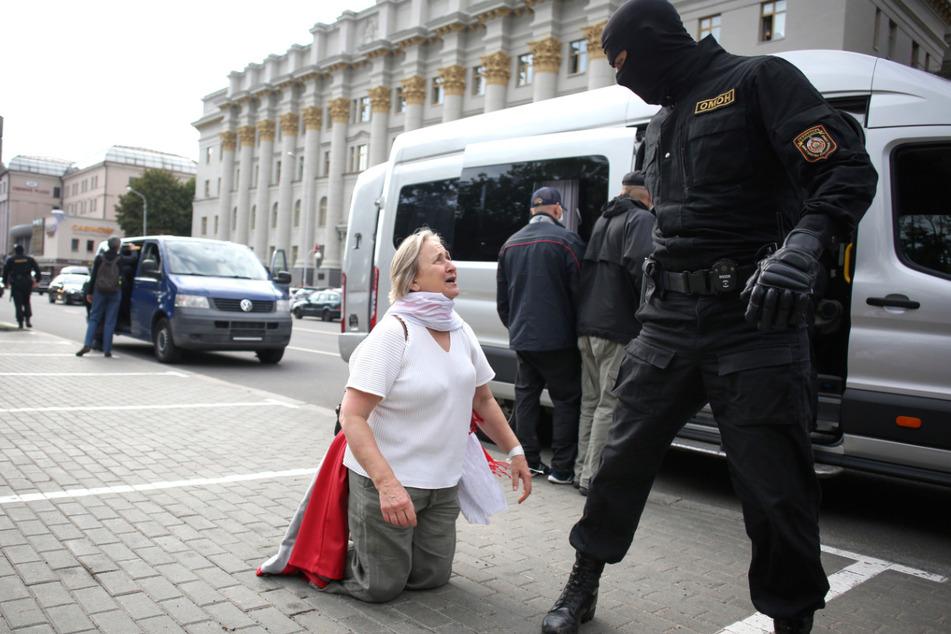 Eine Frau diskutiert mit einem Polizisten während einer Demonstration in Minsk.