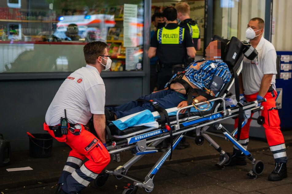 Rettungskräfte transportieren einen verletzten Mann ab. An der Tankstelle war es zu einer Auseinandersetzung gekommen.
