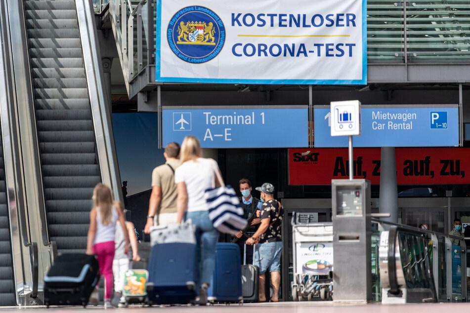 """Reisende gehen am Flughafen in Richtung eines Banners mit der Aufschrift """"Kostenloser Corona-Test""""."""