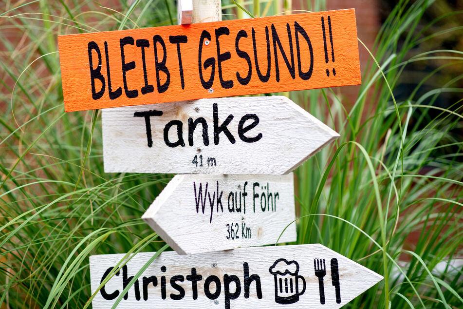"""Ein Holzschild mit der Aufschrift """"Bleibt gesund!"""" hängt an einem Wegweiser, den eine Familie vor ihrem Haus aufgestellt hat."""