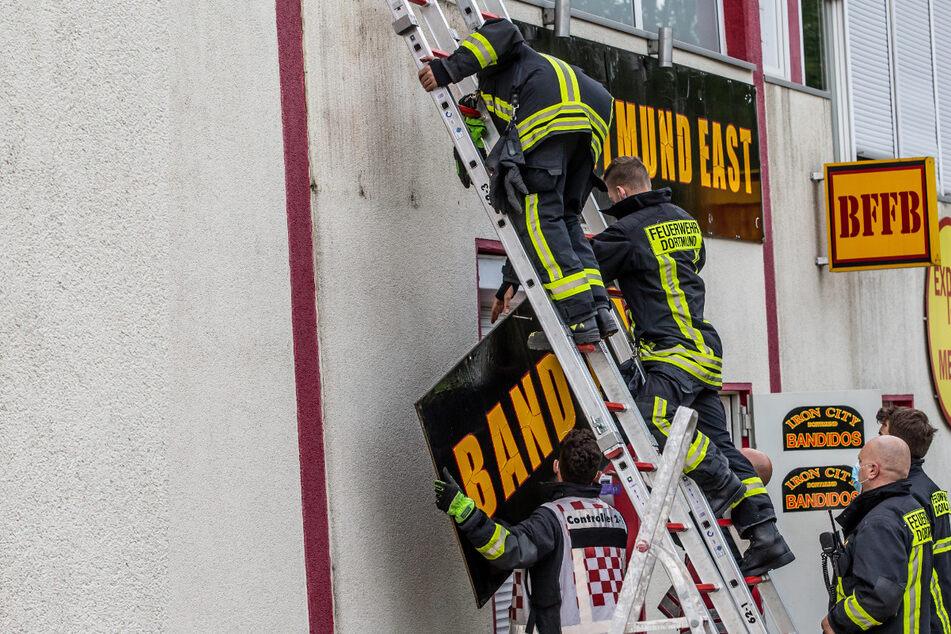 """Feuerwehrleute entfernen unter Polizeischutz ein Schild an einem Vereinsheim der Rockergruppe """"Bandidos""""."""