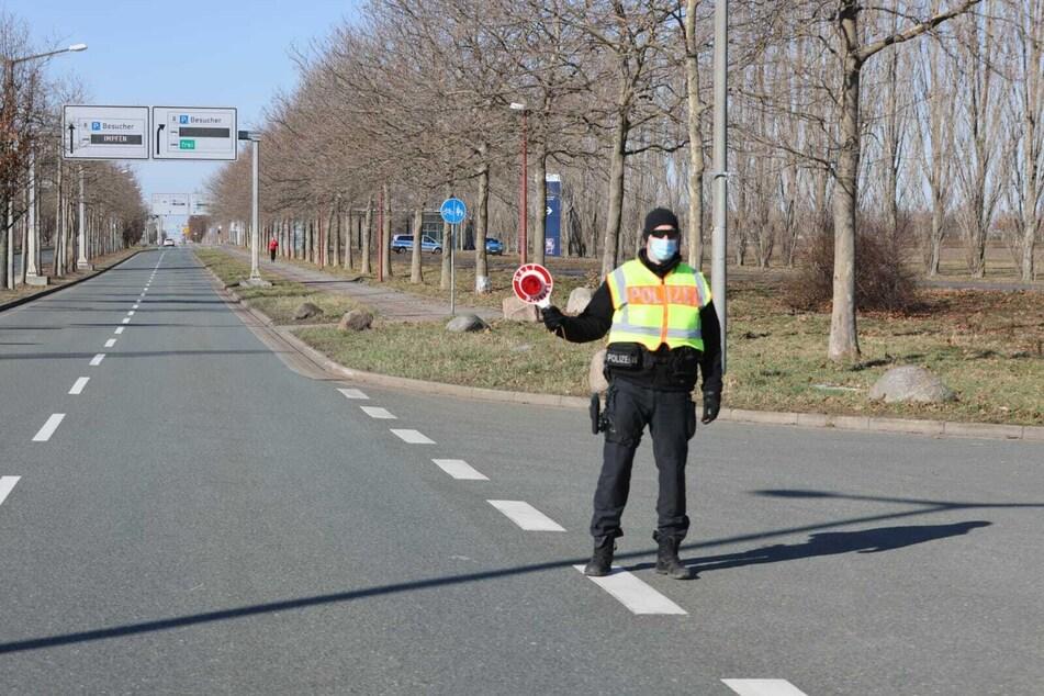 Ein Polizist kontrolliert Autofahrer vor der Neuen Messe im Norden von Leipzig. Ursprünglich sollte ein Autokorso genau dort entlang führen.