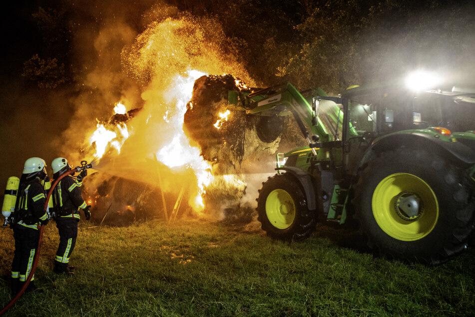 Mithilfe eines Traktors zieht ein Landwirt die brennenden Heuballen auseinander, damit sie besser gelöscht werden können.