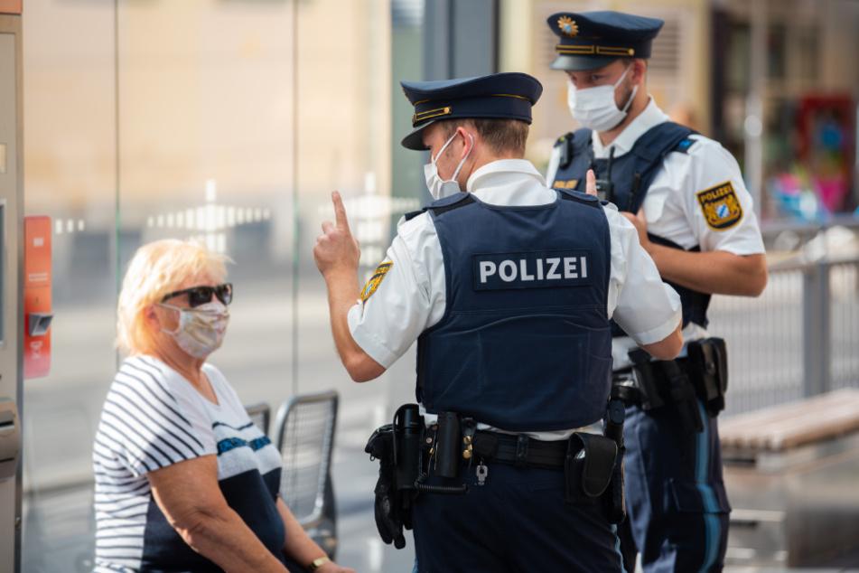 Polizisten belehren eine Frau nach einem Verstoß gegen die Maskenpflicht im öffentlichen Nahverkehr. (Symbolbild)