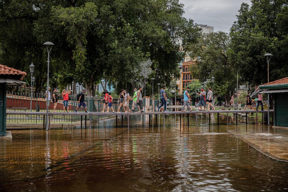 Passanten gehen auf provisorisch angelegten Brücken über eine überschwemmte Straße.