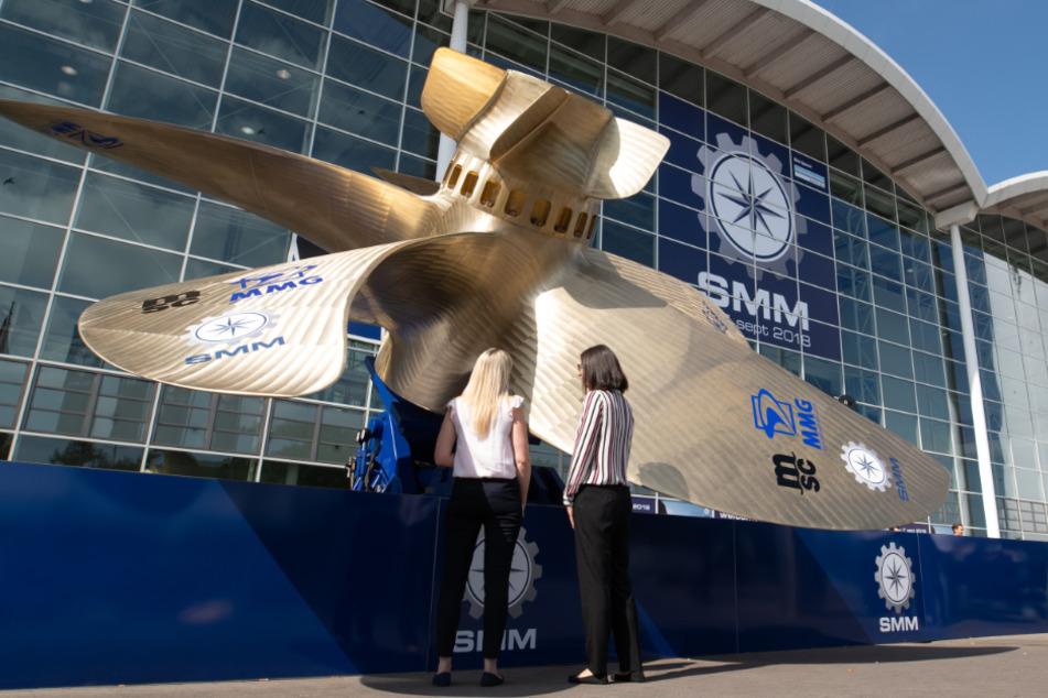 Zwei Frauen betrachten einen riesigen Schiffspropeller vor dem Eingang der Messe SMM für Schiffbau und Meerestechnik. (Archivbild)
