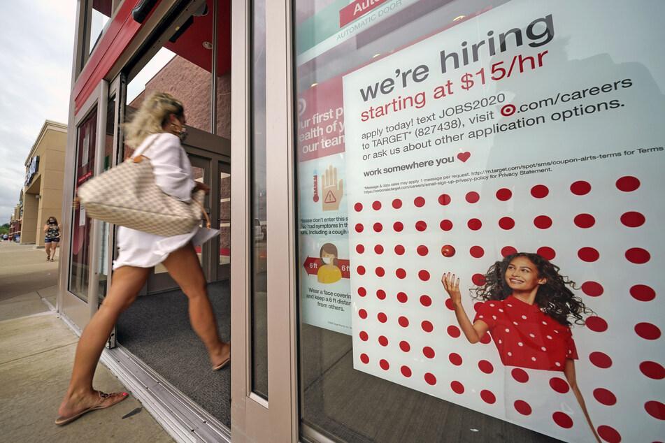"""Ein Schild hängt mit der Aufschrift """"we are hiring"""" (wir stellen ein) an der Tür eines Target-Shops."""