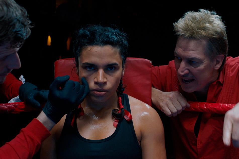 Ali (M., Alina Serban) musste von Kindheit an kämpfen. Aufgeben kommt für sie nicht infrage. Hier wird sie von Trainer Tanne (r., Tobias Moretti) gepusht.