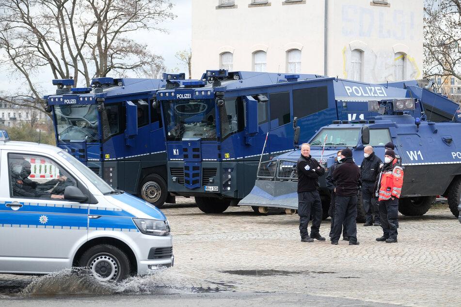 Wasserwerfer und ein Räumfahrzeug der Polizei am Rande einer großen Demo in Dresden.