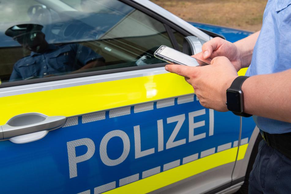 Ein Polizist steht vor seinem Wagen mit einem Smartphone in der Hand (Symbolbild).