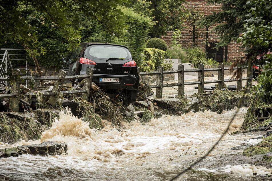 Ein Auto wird von den Wassermassen auf einer überfluteten Straße durch einen Zaun mitgerissen. Teile von Belgien wurden von starken Regenfällen heimgesucht.