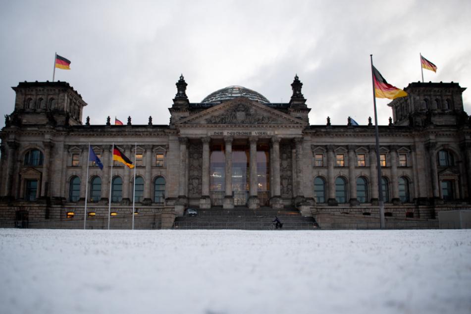 Auf der Wiese vor dem Reichstagsgebäude liegt am Morgen Schnee.
