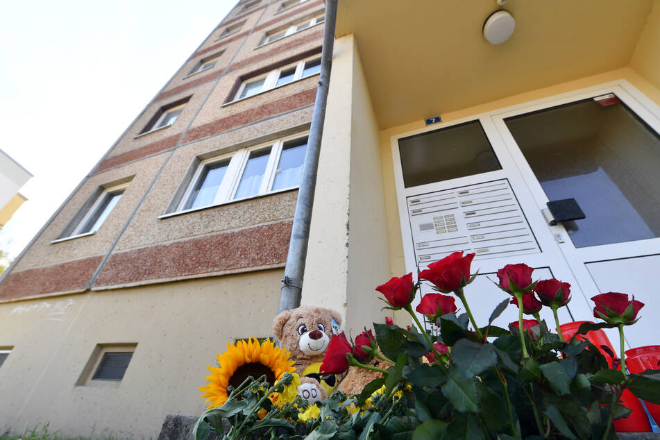 In Gedenken an den zweijährigen Jungen, der am Wochenende tot in einer Wohnung in Querfurt aufgefunden worden war, wurden Blumen und Kerzen vor dem Wohnhaus niedergelegt.