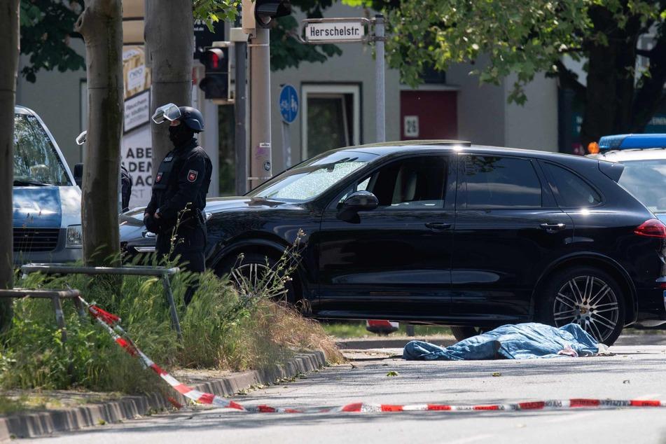 Polizisten sichern einen Tatort an der Herschelstraße, wo neben einem Auto eine abgedeckte Person liegt.