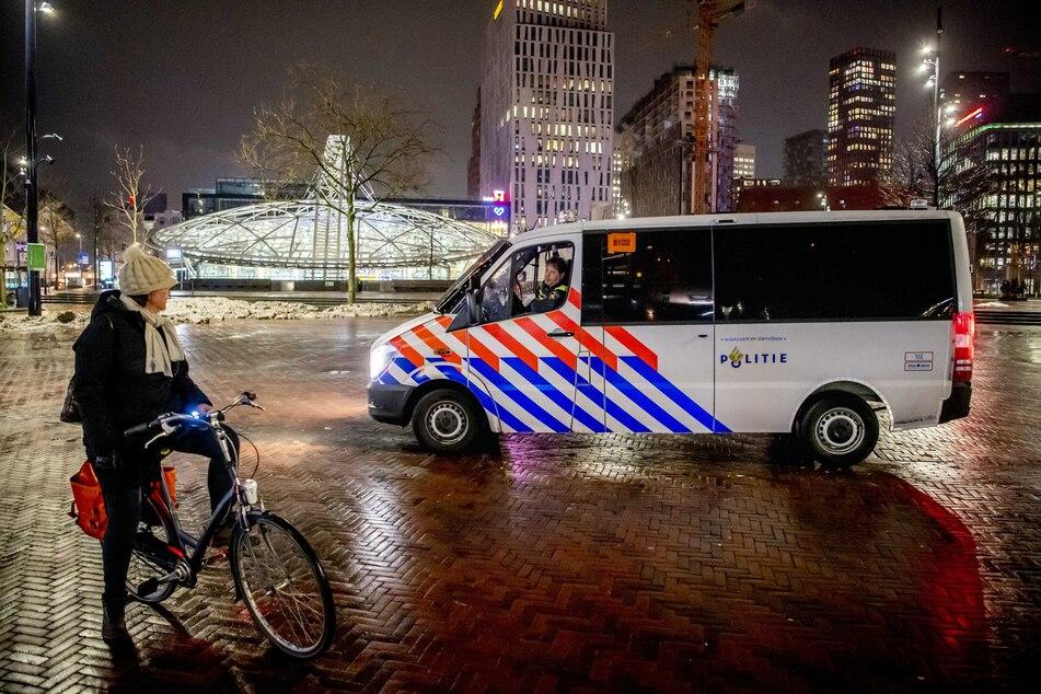 Polizisten im Streifenwagen sprechen eine Frau an, die während der coronabedingten Ausgangssperre am Abend noch in Rotterdam unterwegs ist.