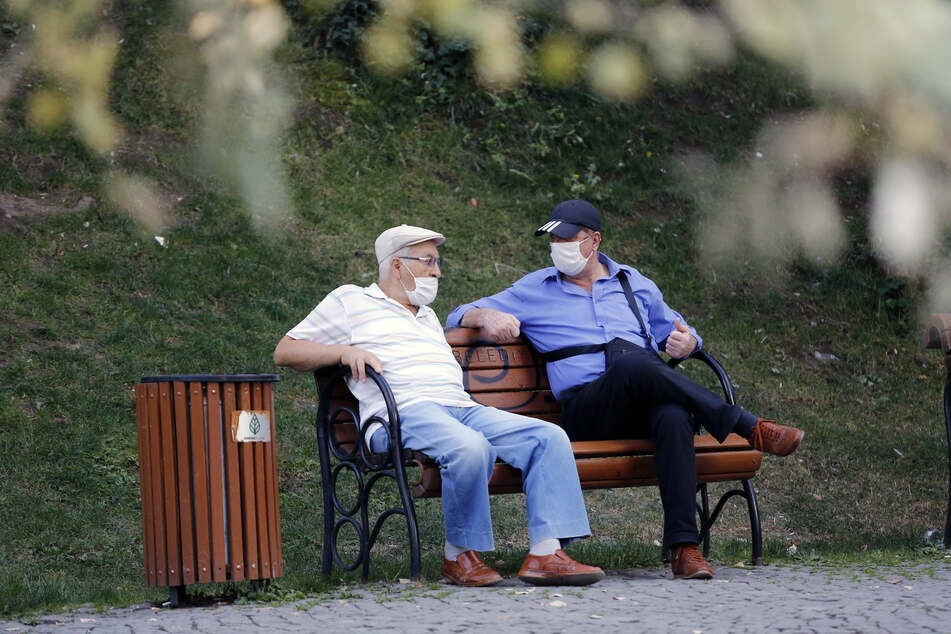 Zwei Männer mit Gesichtsmasken sitzen auf einer Bank in einem Park. Die Türkei bestätigte am Freitag bereits mehr als 1.500 neue Coronavirus-Fälle.