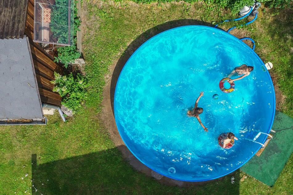 Kinder planschen in einem Pool in einem Garten.