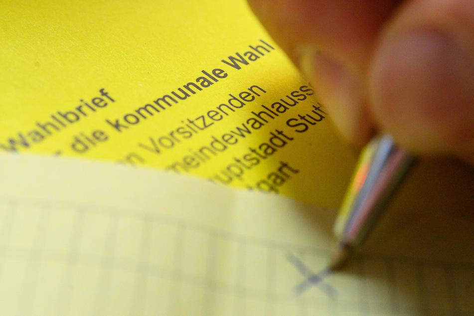 Ein Mann kreuzt einen Wahlzettel der Briefwahl für die Kommunalwahl an.