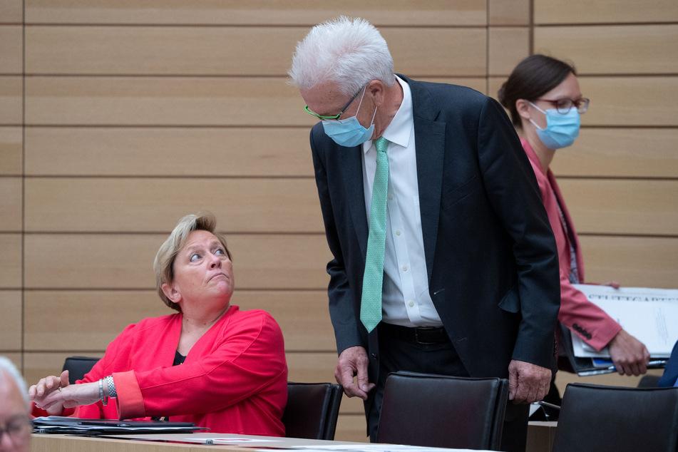 Susanne Eisenmann (CDU, l), Ministerin für Kultus, Jugend und Sport in Baden-Württemberg, unterhält sich während einer Plenarsitzung im Landtag von Baden-Württemberg mit Winfried Kretschmann (Bündnis 90/Die Grünen), Ministerpräsident von Baden-Württemberg.
