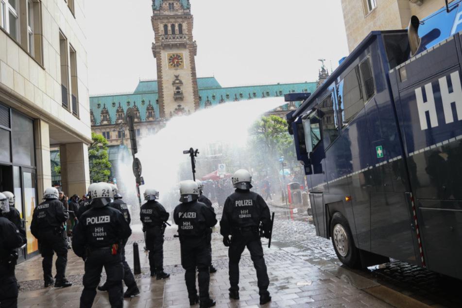 Polizeibeamte setzen nach einer aufgelösten Demonstration am Rathausmarkt einen Wasserwerfer ein. (Archivbild)